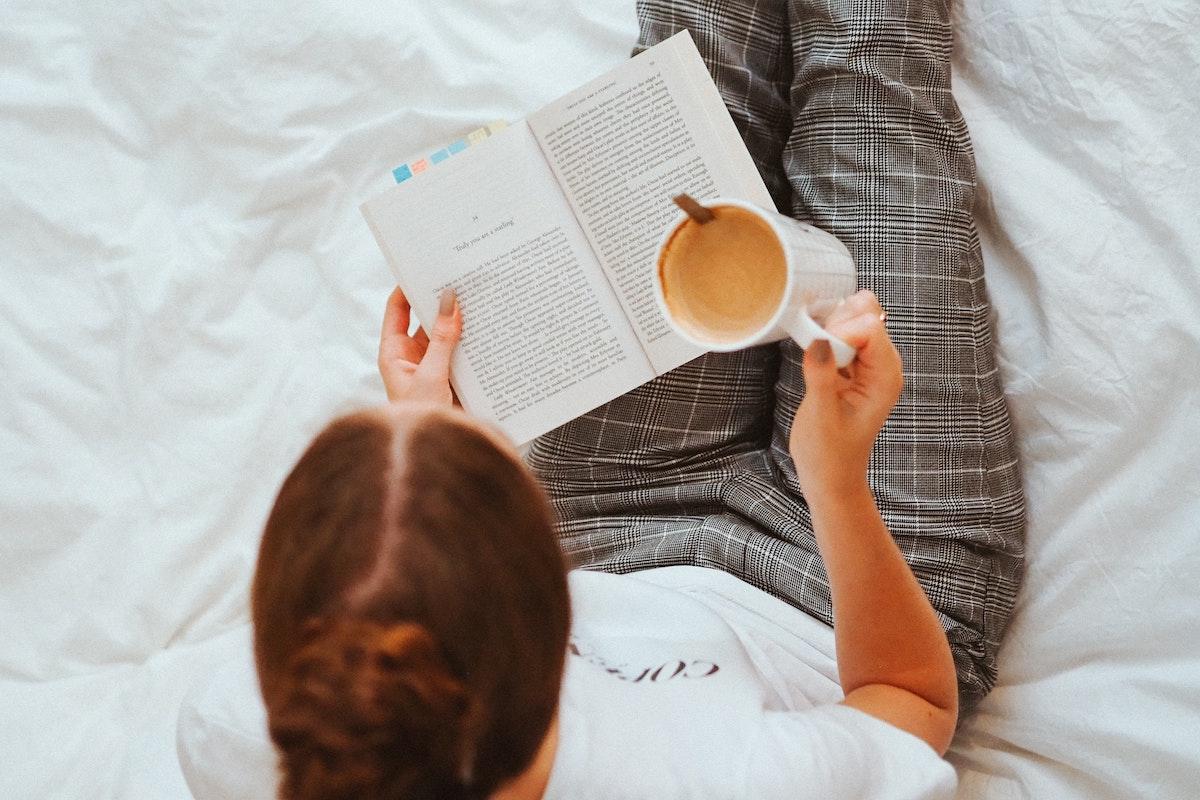 Eine Frau liest ein Buch mit Haftnotizen und hält eine Tasse Kaffee in der Hand
